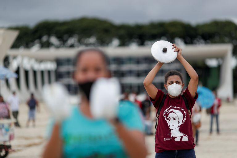 Manifestantes protestam contra o presidete Jair Bolsonaro em frente ao Palácio do Planalto em Brasília nesta segunda-feira, 8 de março.