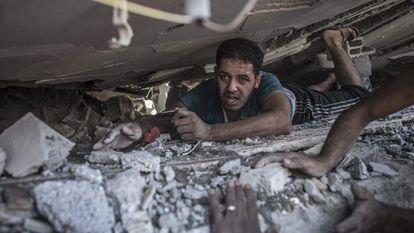 Um palestino faz uma busca entre os escombros.