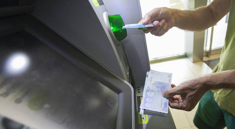 Usuário retira dinheiro de um caixa eletrônico em Madri.