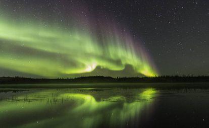 Aurora boreal refletida no lago Prosperous, ao norte de Yellowknife, capital dos Territórios do Noroeste (Canadá).