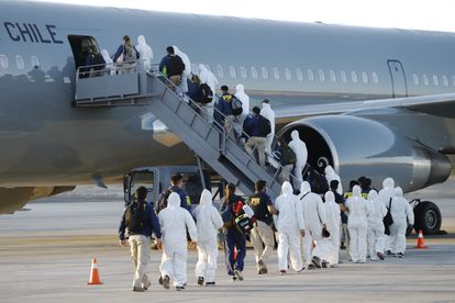 Imigrantes venezuelanos e colombianos são deportados com equipamentos de proteção contra a covid-19, no aeroporto de Iquique, Chile, nesta quarta-feira.