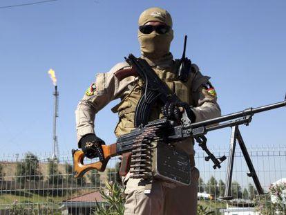 Integrante das forças de segurança curdas vigia refinaria perto de Mossul (Iraque).