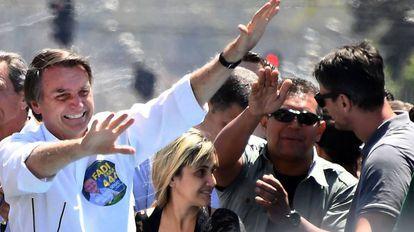 Bolsonaro ladeado por três policiais em carreata em Brasília, no dia 5.