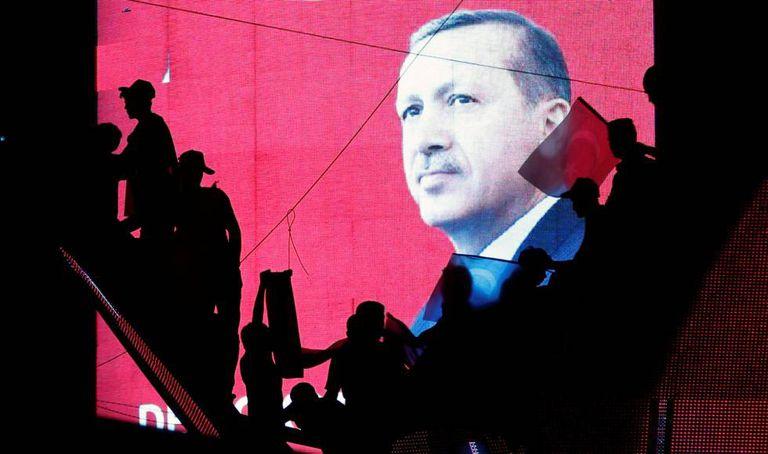 Apoiadores de Erdogan diante de telão.