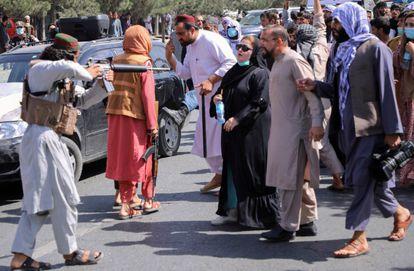 Um miliciano do Talibã aponta sua arma para uma mulher durante uma manifestação em Cabul, na terça-feira. Em vídeo, soldados do novo regime abrem fogo para dissolver protestos.