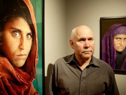 Steve McCurry posa ao lado das fotos de Sharbat Gula em uma exposição em Hamburgo em 2013.