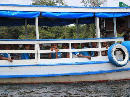 Crianças a caminho da escola, em barco.
