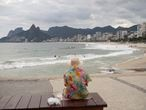 An elderly woman watches Arpoador beach in Rio de Janeiro, Brazil, Tuesday, March 17, 2020. Firemen began blaring recordings that urge beachgoers to stay home on Monday, one day before Rio's Gov. Wilson Witzel decreed a state of emergency. For most people, the new coronavirus causes only mild or moderate symptoms, such as fever and cough. For some, especially older adults and people with existing health problems, it can cause more severe illness, including pneumonia. (AP Photo/Silvia Izquierdo)