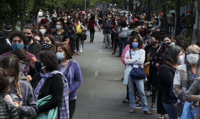 Chilenos fazem fila para votar no plebiscito deste domingo, na capital Santiago.
