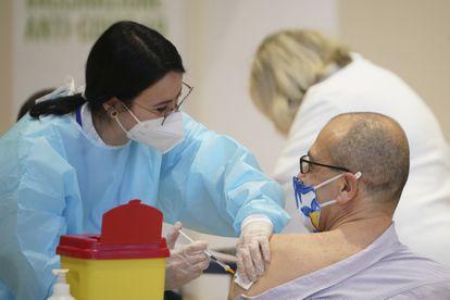 Agente de saúde vacina com uma dose da AstraZeneca um homem na quarta-feira.