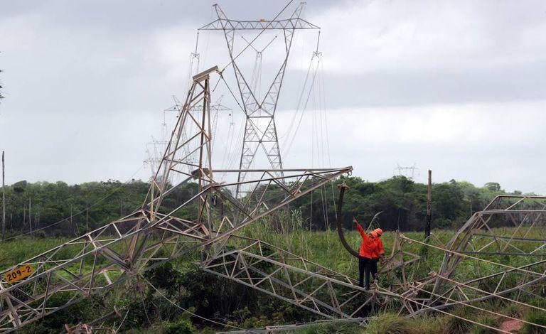 Técnicos reparam rede de transmissão atingida por bomba na periferia de Fortaleza.
