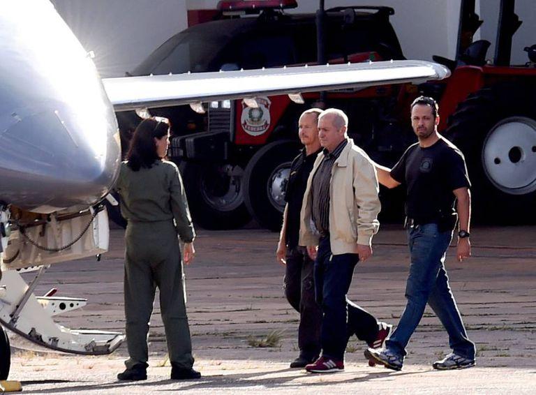 Paulo Bernardo, de jaqueta clara, é conduzido para avião da PF.