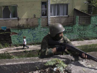 Uma menina passa por um soldado armado, durante uma operação surpresa na Cidade de Deus, no Rio de Janeiro.