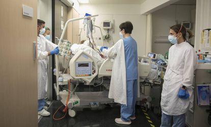 A intensivista Ana Zapatero (à direita) acompanha a paciente Raquel Txavarria a uma sala de neuroangiografia do Hospital del Mar, em dezembro.