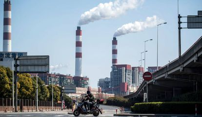 Um motociclista passa em frente a chaminés de uma central de geração elétrica em Xangai (China).
