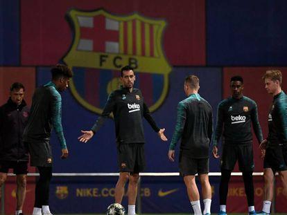 Busquets gesticula com companheiros em treino do Barcelona.
