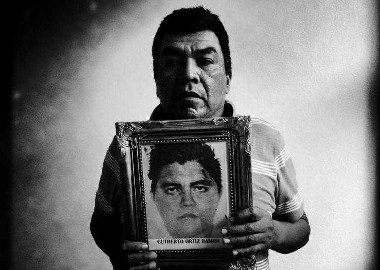 Oscar Ortiz Serafin segura a foto de seu filho Cutberto Ortiz Ramos em uma sala de aula transformada em dormitório para as famílias dos alunos desaparecidos da Escola Rural de Ayotzinapa.
