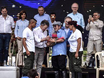 Guerrilheiros entregam bebê a Rodrigo Londoño, líder das FARC, e ao presidente Juan Manuel Santos em ato de entrega das armas