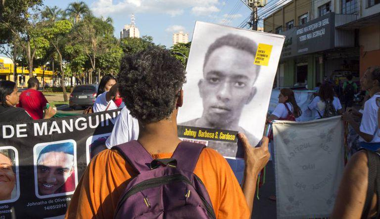 Ativista mostra imagem de rapaz vítima da violência do Estado.