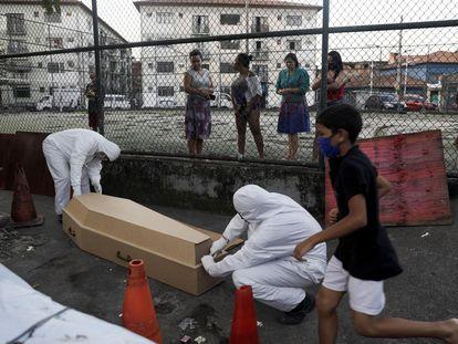 Funcionários de uma funerária levam de uma favela no Rio de Janeiro o cadáver que, segundo a vizinhança, levou 30 horas para ser recolhido.