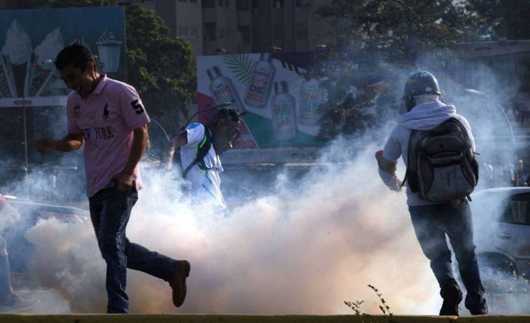 Vários manifestantes tentam se proteger das bombas lacrimogêneas nesta terça em Caracas.