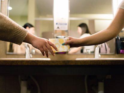Uma pessoa entrega um absorvente a outra num ambiente escolar.
