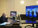 Russian President Vladimir Putin participates in a video call with Moscow Mayor Sergei Sobyanin, left, Alexander Dyukov Chairman of the management Board of Gazprom Neft, center, and Russian Minister of Energy Alexander Novak at the Novo-Ogaryovo residence outside Moscow, Russia, Thursday, July 23, 2020. The call was linked to the launch of a new production facility at Moscow's oil refinery. (Alexei Druzhinin, Sputnik, Kremlin Pool Photo via AP)
