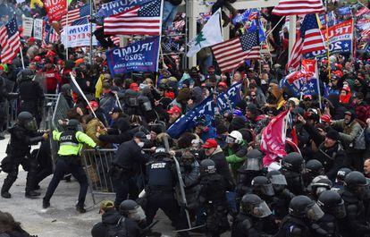 Multidão de seguidores de Donald Trump quebra a barreira de segurança levantada pela polícia diante do Capitólio em 6 de janeiro.
