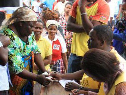Uma eleitora apresenta sua documentação em um posto de votação em Maputo, nesta quarta-feira.