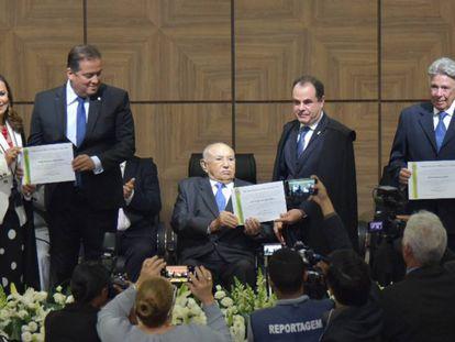 Eduardo Gomes (esq.) é diplomado senador pelo Estado do Tocantins junto dos suplentes Siqueira Campos (sentado) e Ogari Pacheco (dir.)
