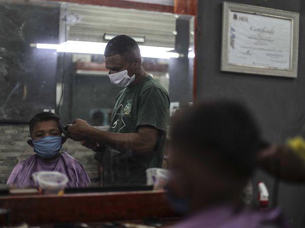 AME4443. RÍO DE JANEIRO (BRASIL), 21/04/2020.- Un barbero de la favela de Mandela trabaja con tapabocas este martes durante la pandemia COVID-19, en la zona norte de Río de Janeiro (Brasil). EFE/Antonio Lacerda