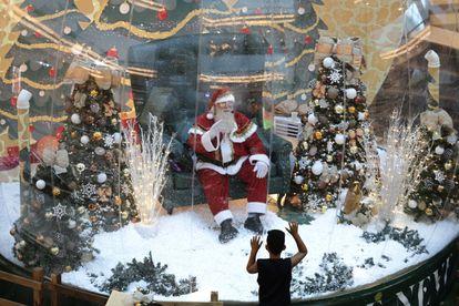 Abilio Nunes, artista do Papai Noel, acena para crianças de dentro de uma bolha, em um shopping de Brasília.