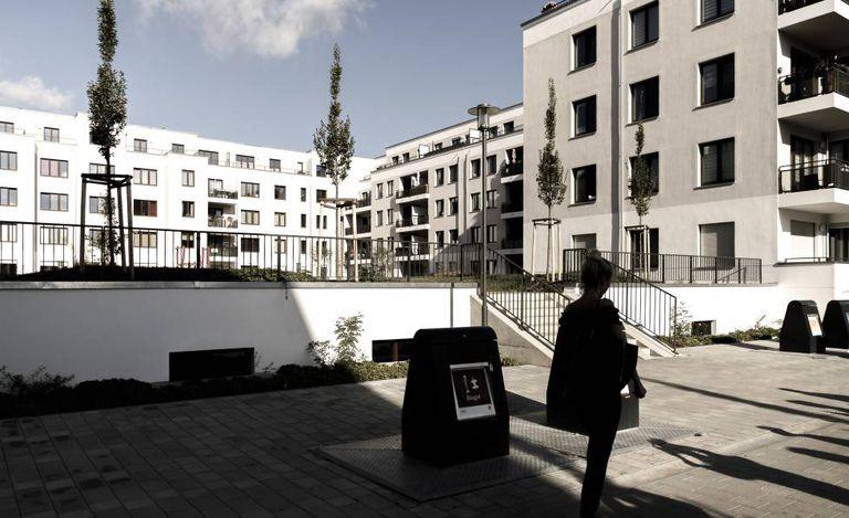 Uma mulher passa em frente a um complexo residencial em Berlim.
