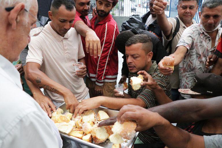 Pessoas em situação de rua recebem acolhimento e comida na paróquia São Miguel Arcanjo, na Mooca, zona leste de São Paulo.