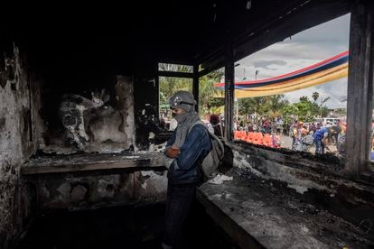 Jovem monta guarda dentro de uma delegacia de polícia que foi incendiada por manifestantes em Puerto Resistencia, Cali, nesta quarta-feira.