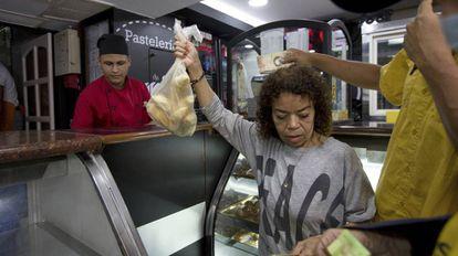 Clientes compram pão subsidiado em uma confeitaria de Caracas
