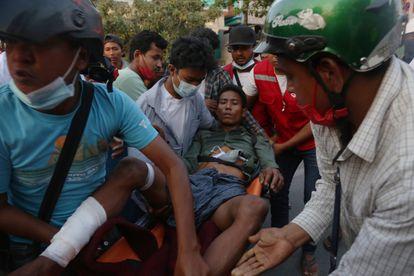 Translado de um homem depois que a polícia reprimiu aos manifestantes em um protesto em Mandalay (Myanmar), este domingo.