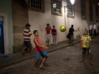 Meninos jogam bola em uma rua de Salvador.