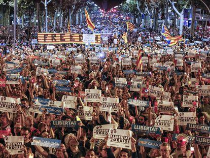 """Vista geral de uma multidão de manifestantes que portam cartazes nos quais se pode ler """"Help Catalonia"""" e """"Freedom"""", durante a manifestação."""