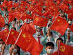 Students wave flags of China and the Communist Party of China before celebrations in Beijing on July 1, 2021, to mark the 100th anniversary of the founding of the Communist Party of China. (Photo by WANG Zhao / AFP)