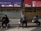 Pedestrians sit on benches outside of shuttered stores in Santiago, Chile, on Thursday, Sept. 2, 2021. Chile's central bank raised its 2021 growth and inflation forecasts as the economy runs hot, a day after policy makers delivered the biggest interest rate increase in two decades. Photographer: Tamara Merino/Bloomberg