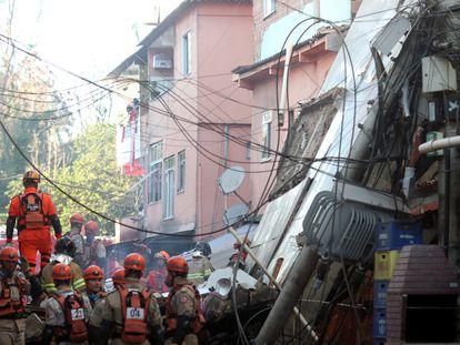 Bombeiros buscam vítimas entre os escombros do edifício que desabou na madrugada de desta quinta-feira na comunidade de Rio das Pedras, no Rio.