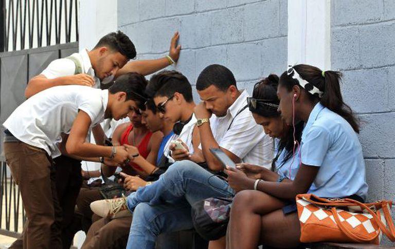Jovens acessam a Internet no primeiro ponto de wifi gratuito de Cuba.