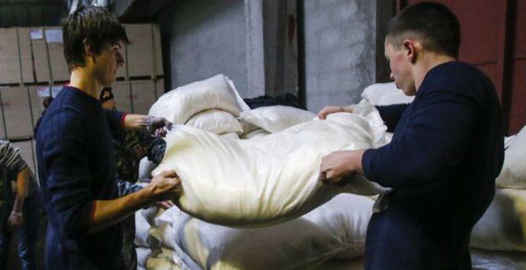 Dois homens levantam um saco com ajuda humanitária em Makeyevka, na região de Donetsk.