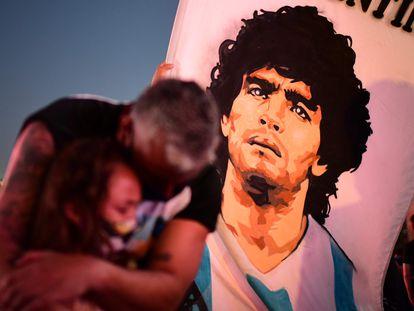 Pai abraça a filha durante manifestação no Obelisco de Buenos Aires em homenagem ao astro Diego Armando Maradona.