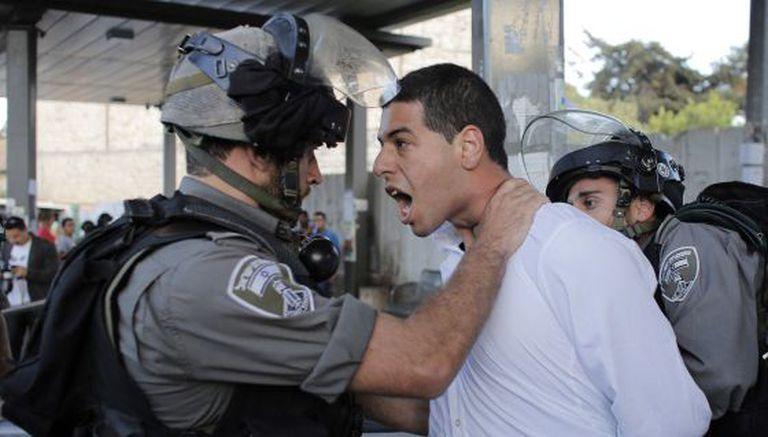 Um policial israelense prende um palestino em protesto em Jerusalém.