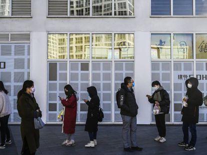Trabalhadores na porta de seu escritório em Pequim.