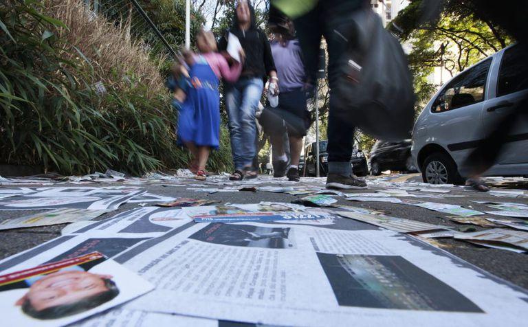 Pedestres próximo a local de votação com santinhos no chão em São Paulo, na eleição presidencial.