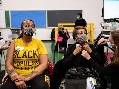 Andrea Morre (esq.) aguarda com sua mãe, Alma Penn, para se vacinar nesta sexta-feira no colégio Whitney M. Young de Louisville (Kentucky)
