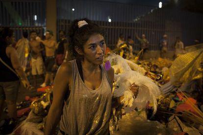 Uma mulher entre os restos das fantasias usadas para o desfile.